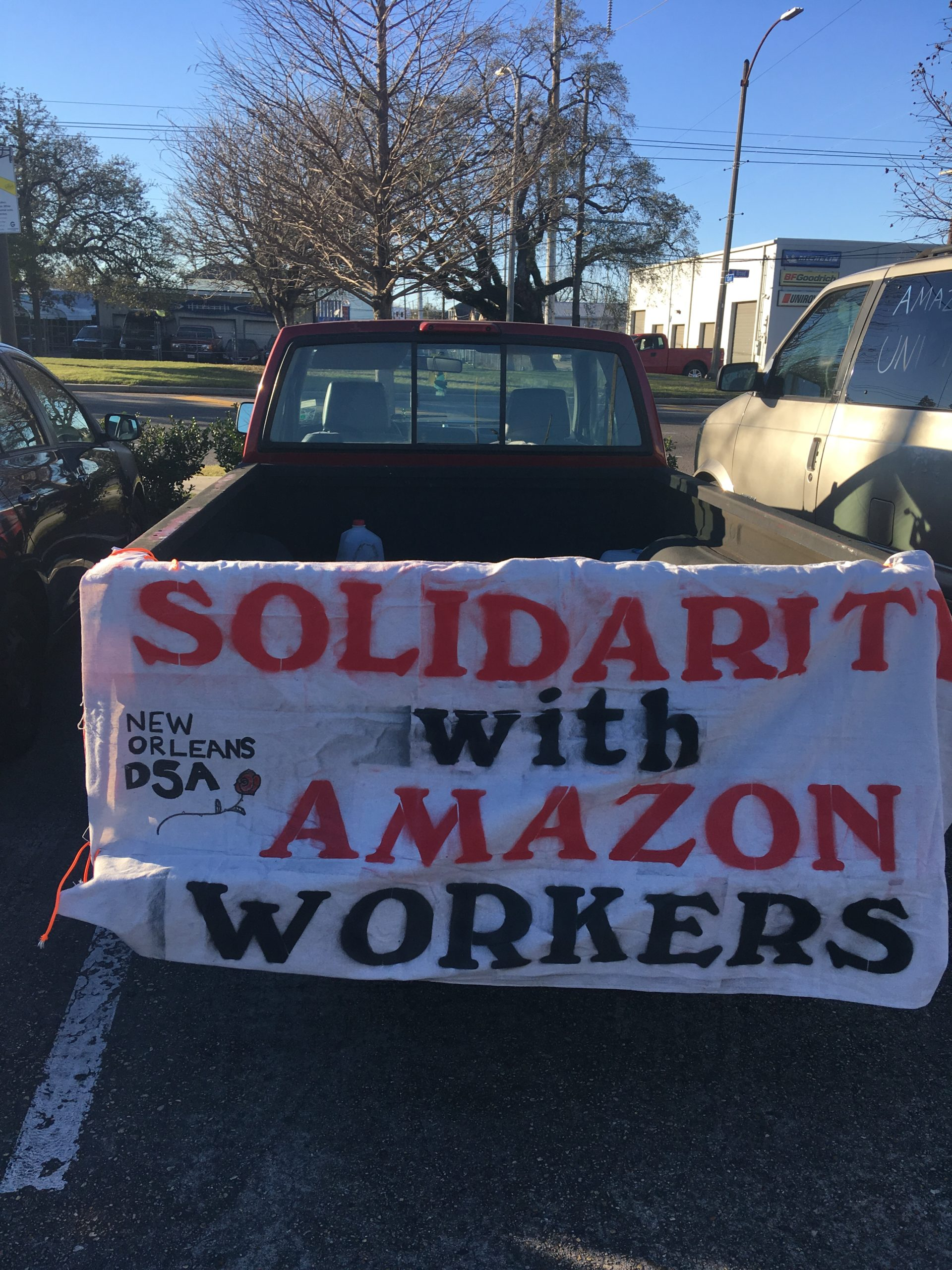 """pickup truck with a banner on the tailgate reading """"Solidarity with Amazon Workers"""" and """"New Orleans DSA 🌹"""""""